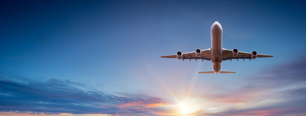 A commercial airplane flying as the sun sets.