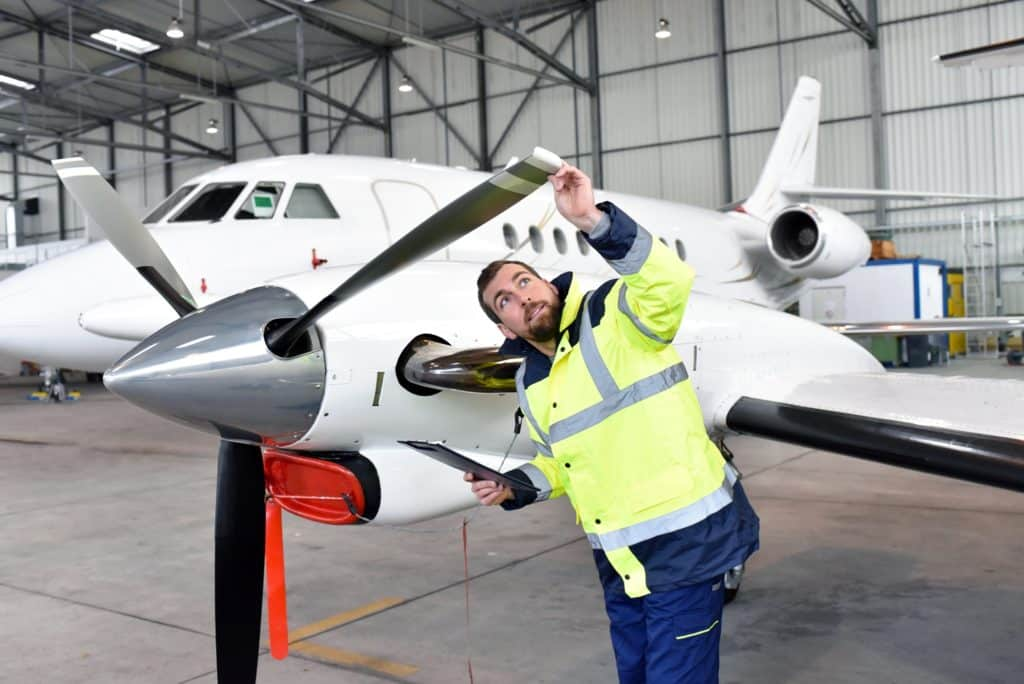 An airplane mechanic checking a propellor of a small plane seeing if it needs any cold spray repairs