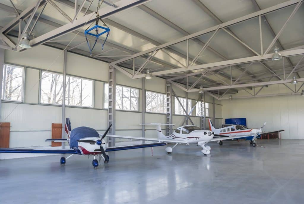 Three small aircraft being stored in air dock.